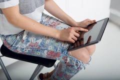 Sluit van een meisjesholding op zijn knie omhoog een tablet en raak het scherm met vinger De persen van de hand op het scherm dig stock afbeelding