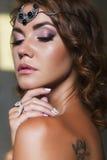 Sluit van een mooie donkerbruine vrouw met maken omhoog omhooggaand en krullend Ha Royalty-vrije Stock Fotografie
