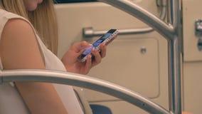 Sluit van Gebruik van de Hand het Jonge Kaukasische Vrouw omhoog de Ritten van Smartphone Apps in Metro stock video