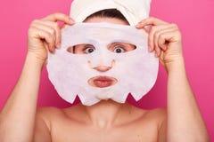 Sluit van grappige vrouw kijkt door Witboekmasker, heeft gezichtsbehandelingen, draagt omhoog handdoek op hoofd, zorgen van schoo royalty-vrije stock foto