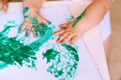 Sluit van hand omhoog weinig kindtekening met groene verf op de herfstbladeren stock afbeelding