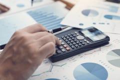 Sluit van handinvesteerders uitputten calculators om de inkomens van het bedrijf te berekenen om in voorraden voor toekomstige wi stock fotografie