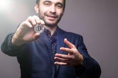 Sluit van Handome-de bedrijfsdiemens bitcoin op camera op donkere achtergrond wordt gericht met tonned omhoog licht Stock Fotografie