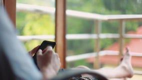 Sluit van het gebruik van mensenhanden omhoog mobiele telefoonzitting door een venster tijdens een de zomerregen op de tropische  stock video