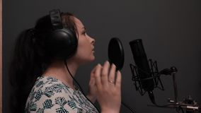 Sluit van jong mooi meisje registreert omhoog lied in professionele studio met grijze muren stock footage