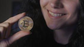 Sluit van Jonge vrouw tegenhoudt gouden Bitcoin in hand mijnbouw en handel stock footage