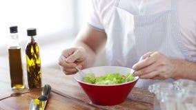 Sluit van mannelijke handen mengt salade in een kom stock footage