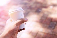 Sluit van mannelijke handholding weghalen omhoog koffiekop bij ochtendti stock foto's