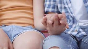 Sluit van meisje en jongen en onhandig schuchter opnemen elkaars hand Een paar gelukkige kinderen die op de bank zitten stock footage