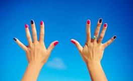 Sluit van omhoog open handen met kleurrijke spijkers Stock Fotografie