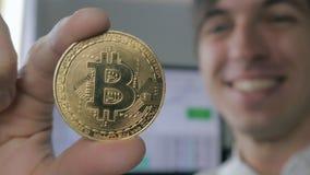 Sluit van Verbaasde Verraste Jonge Zakenman tegenhoudt BTC in hand Bitcoin Succes op inkomens in de crypto-munt stock video