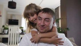 Sluit van vrolijk tienermeisje met lang haar koestert omhoog haar papa en thuis lacht in de woonkamer Vader en van hem stock videobeelden