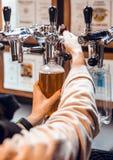 Sluit van vrouw overhandigt het vullen omhoog plastic fles ambachtbier in massa royalty-vrije stock afbeeldingen