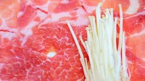 Sluit verse ruwe marmervarkensvleesdia en omhoog gouden die naaldpaddestoel of enokipaddestoel op plaat voor shubu, BBQ grill in  stock fotografie