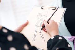 Sluit vrouw die bij kledingstukfabriek schets met ontwerp voor nieuwe kleding omhoog maken stock afbeelding