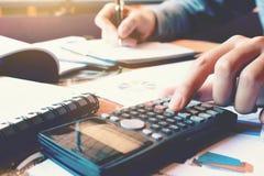 Sluit vrouwenhand het drukken omhoog calculator en het doen van financiën bij hom Royalty-vrije Stock Afbeeldingen