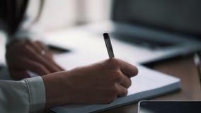 Sluit vrouwenhand schrijven nota's met pen in notitieboekje, langzame motie stock video