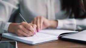 Sluit vrouwenhand schrijven nota's met pen in notitieboekje, langzame motie stock footage