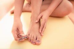 Sluit vrouwenhanden snijdt omhoog haar voetenspijkers in slaapkamer stock foto's