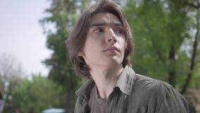 Sluit zitting die van de portret omhoog de eenzame zenuwachtige jonge mens op de bank in het park op zijn vriend of meisje wachte stock videobeelden