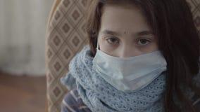 Sluit zitting van het portret omhoog de droevige zieke meisje in de leunstoel met een steriel masker op haar gezicht binnen r stock video