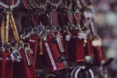 Sluiten de rode postbus van Londen en de rode busherinnering kettingen op verkoop bij een straatmarkt in Londen, het UK royalty-vrije stock afbeeldingen