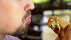 Sluiten man die een hamburger eet in een fastfoodrestaurant stock footage