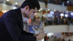 Sluiten-op schot van een zakenman die een mobiele telefoon in winkelcomplex met behulp van stock video