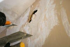 Sluitende gaten in de muur met stopverf Het reparatiewerk stock fotografie