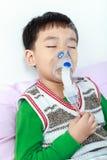 Sluitende ogen van het close-up houdt de Aziatische kind en een inhaleertoestel van de maskerdamp stock foto