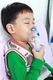 Sluitende ogen van het close-up houdt de Aziatische kind en een inhaleertoestel van de maskerdamp stock afbeelding