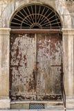 Slum door. An old, rusty wooden door with lot of scratches and peeling paint Stock Image