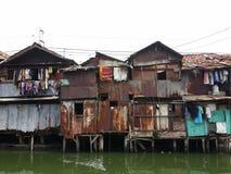 Slum in Jakarta. Rundown houses on the riverbank in Jakarta Stock Photos