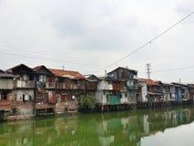Slum in Jakarta. Rundown houses on the riverbank in Jakarta Stock Images
