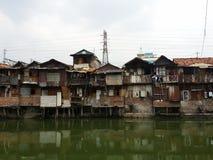Slum in Jakarta. Rundown houses on the riverbank in Jakarta Royalty Free Stock Photos