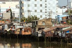 Slum in Saigon. Slum wooden house on the Saigon river bank, in front of modern buildings, in Ho Chi Minh city, Vietnam royalty free stock photography