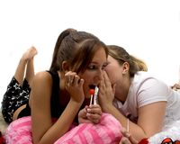Slumber party. 2 young ladies sharing a secert while enjoying some lollipops Royalty Free Stock Images