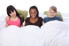 Slumber party fun happy teenage girls in bed Stock Images