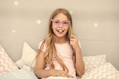 Slumber party photo booth props. Kid girl cheerful posing with pink eyeglasses party attribute. Prepare photo booth. Props hand made or buy for party. Look at royalty free stock images
