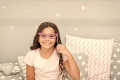 Slumber party photo booth props. Kid girl cheerful posing with retro pink eyeglasses party attribute. Prepare photo. Booth props hand made or buy for party royalty free stock image