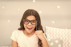 Slumber party photo booth props. Kid girl cheerful posing with vintage black eyeglasses party attribute. Prepare photo. Booth props hand made or buy for party royalty free stock photo