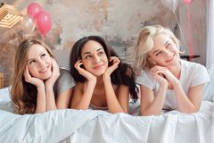 Slumber Party. Young women together at home lying on bed looking aside dreamful close-up stock photography