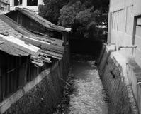 Slumkvarter nära smutsar ner diket i det svarta vita temafotoet som tas i Jakarta Indonesien Royaltyfri Foto