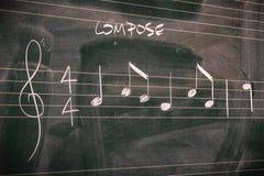 Slumpmässiga musikanmärkningar på en svart tavla royaltyfria bilder