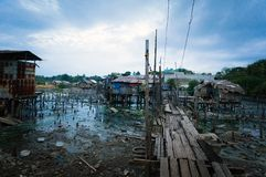 Slums in Asia. Philippine slums on the island of Palawan, dirty poor house standing on stilts on the water Royalty Free Stock Photos