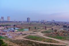 Slums, empty farm feilds with high rise buildings in the background in gurgaon delhi NCR. Shows the contrast of housing in india`s cities with slums and luxury stock image