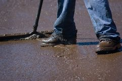 Slurry. Feet of a workman spreading slurry sealer over an asphalt roadway royalty free stock image