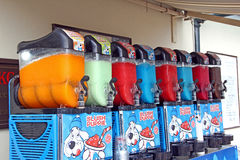 Slush puppie multi coloured drinks machine. Photo of multi coloured slush puppie ice drinks in container machine Stock Images