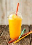 Slushie congelato arancio in tazza di plastica con paglia Immagine Stock