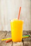 Slushie congelato arancio in tazza di plastica con paglia Immagine Stock Libera da Diritti